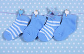 Baby boy nursery blue socks and butterfly hanging from pegs on a — Stock Photo