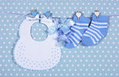 Baby boy nursery blue socks and bib, with dummy pacifier hanging — Stock Photo