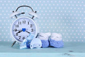 Baby boy nursery blue and white booties and clock, on aqua vinta — Stock Photo