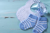 Baby boy nursery blue and white socks, bib and dummy pacifier, w — Stock Photo