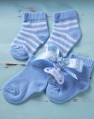 Baby boy nursery blue and white socks and dummy pacifier, on aqu — Stock Photo