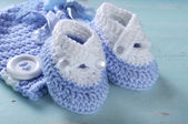 Baby boy nursery blue and white wool booties and bonnet close up — Stock Photo