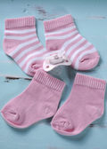 Baby girl nursery pink and white stripe socks and pacifier dummy — Stock Photo