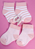 Baby girl nursery pink and white stripe socks and dummy pacifier — Stock Photo