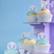 Blue theme baby boy cupcakes on purple polka dot cupcake stand — Stock Photo #46422247