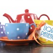 Red, blue, yellow, orange and purple polka dot tea set with teapot, milk jug creamer, sugar bowl and tea cup with sample text Liquid Patience — Stock Photo #50548691