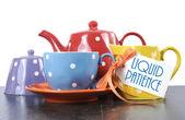 Czerwony, niebieski, żółty, pomarańczowy i fioletowy kropki zestaw herbaty z czajnik, dzbanek mleka śmietanki, cukiernica i kubek herbaty z próbki ciekłej tekst cierpliwości — Zdjęcie stockowe