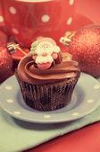 Magdalenas de chocolate navidad con caras santa contra un festival rojo — Foto de Stock