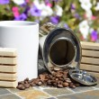Photo: White coffee mug and canister of spilled coffee beans