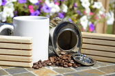 White coffee mug and a canister of spilled coffee beans — Stock Photo