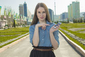 Beautiful girl using smart phone in background city — Stock Photo