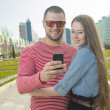 Happy man and woman using smartphone — Stockfoto