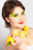 Asian girl with lemon in her hand and with lemons on her neck — Stock Photo
