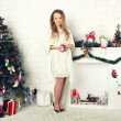 Stock Photo: Young girl in red dress with gift near Christmas tree