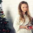 Young girl in red dress with gift near Christmas tree — Stock Photo #37870979