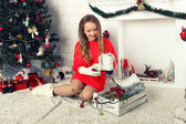 Young girl in a red dress with skates near the Christmas tree — Stok fotoğraf