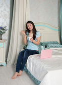 Woman with a laptop to eat yogurt in bed — Stock Photo
