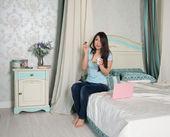 женщина с ноутбуком съесть йогурт в постели — Стоковое фото