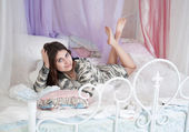 L woman in bed in a white shirt — Stock Photo