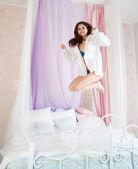 Vrouw springen op het bed — Stockfoto