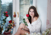 Woman in the flowers on the windowsill — Stock Photo