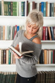 Blonde holding a book in bookshelf — Stock Photo