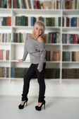 Woman standing at bookshelf — Stock Photo