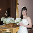 Bride near mirror in wedding palace — Stock Photo #25239975