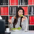 Stock Photo: Business woman eating salad for lunch.