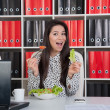 Business woman eating salad for lunch. - Stock Photo