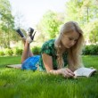 Girl is laying on the grass with a book — Stock Photo