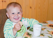 Healthy baby is drinking at a table — Stock Photo