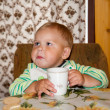 Little boy is drinking at a table — Stock Photo