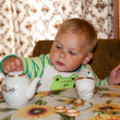Year-old boy pours tea into a cup — Stock Photo