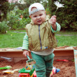 Builder boy playing in a sandbox — Stock Photo