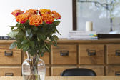 Orange roses on dining table interior scene — Stock Photo