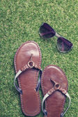 Summer sandals and sunglasses on grass — Stock Photo