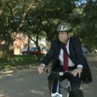 A businessman using an eco-friendly mode of transportation stops his bicycle and checks for traffic. — Stock Video #26641415