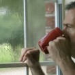 A handsome mature man enjoys a cup of coffee as he watches a summer rain shower through his window. — Stock Video #26641489