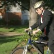 An environmentally mindful businessman reduces his carbon footprint by using a bicycle instead of his car to get to work. — Stock Video