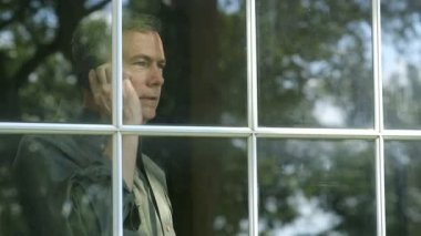 A handsome mature man standing by a window engaged in pleasant conversation on his cell phone. — Stock Video