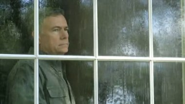 A pensive mature man watches a summer rain shower from his living room window. — Stock Video