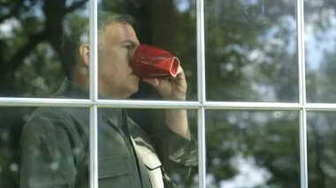 Outside window view of a handsome mature man on a bright sunny day enjoying a cup of coffee. — Stock Video