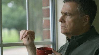 Handsome mature man gazes out a window on a bright sunny day while enjoying his coffee. — Stock Video
