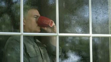 Outside window view of a handsome mature man enjoying a cup of coffee as he watches a summer rain shower. — Stock Video