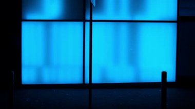 Silhouettes in front of a blue illuminated glass wall — Stock Video