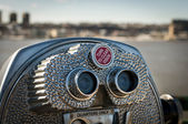 Tourist binoculars with city in background — Stock Photo