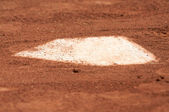 A baseball home plate is surrounded by dirt and shallow depth of field. — Stock Photo