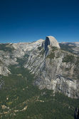 Clear skies let the sun shine down on Half Dome inside of Yosemitie National Park. — Stock Photo