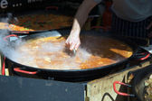 Cooking food in large pot in outdoor street market — Stock Photo